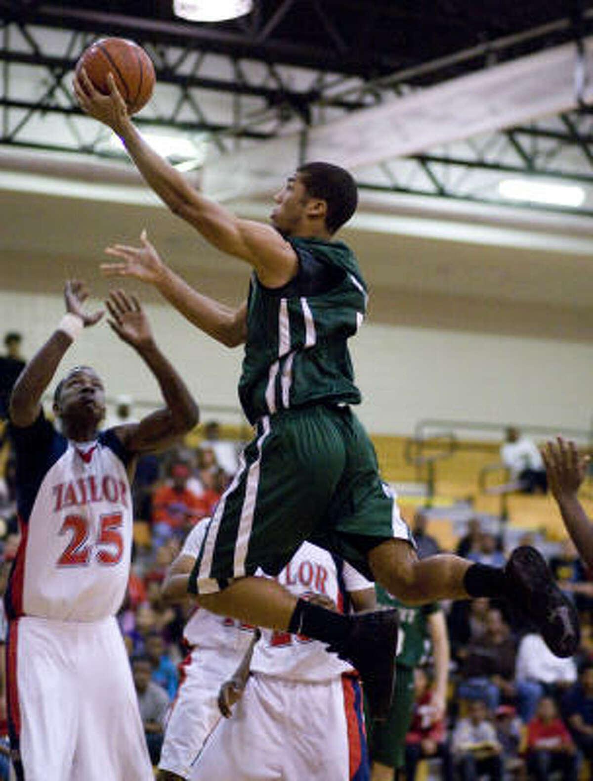 Strake Jesuit's Joey Brooks goes to the basket over Alief Taylor's Josh Greenwood (25).