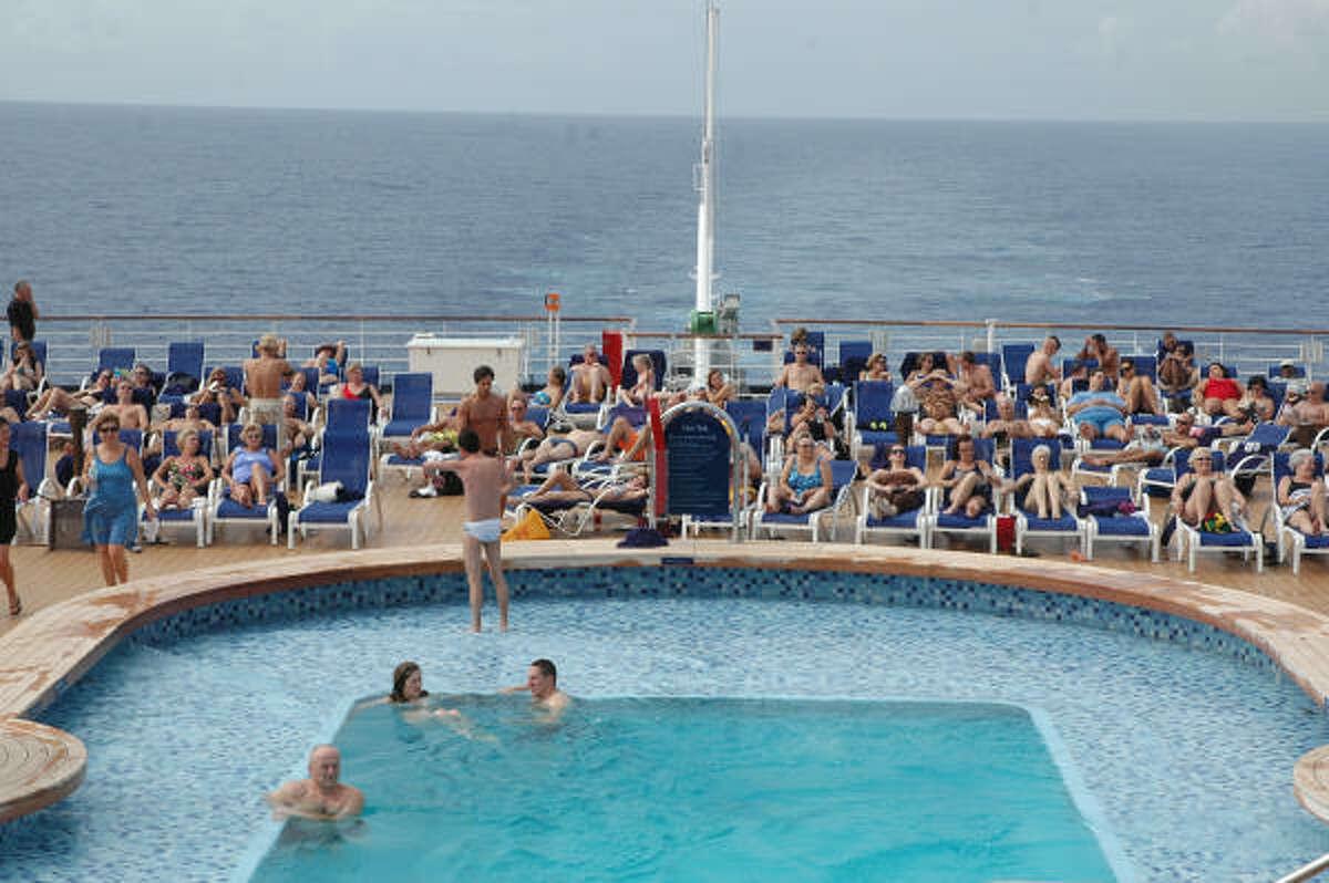 Passengers on Holland America's Eurodam swim and sunbathe beside one of the ship's pools.