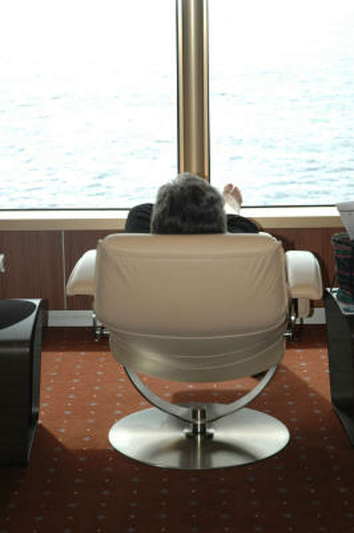 A passenger aboard Holland America's Eurodam relaxes barefoot while looking out at the ocean.