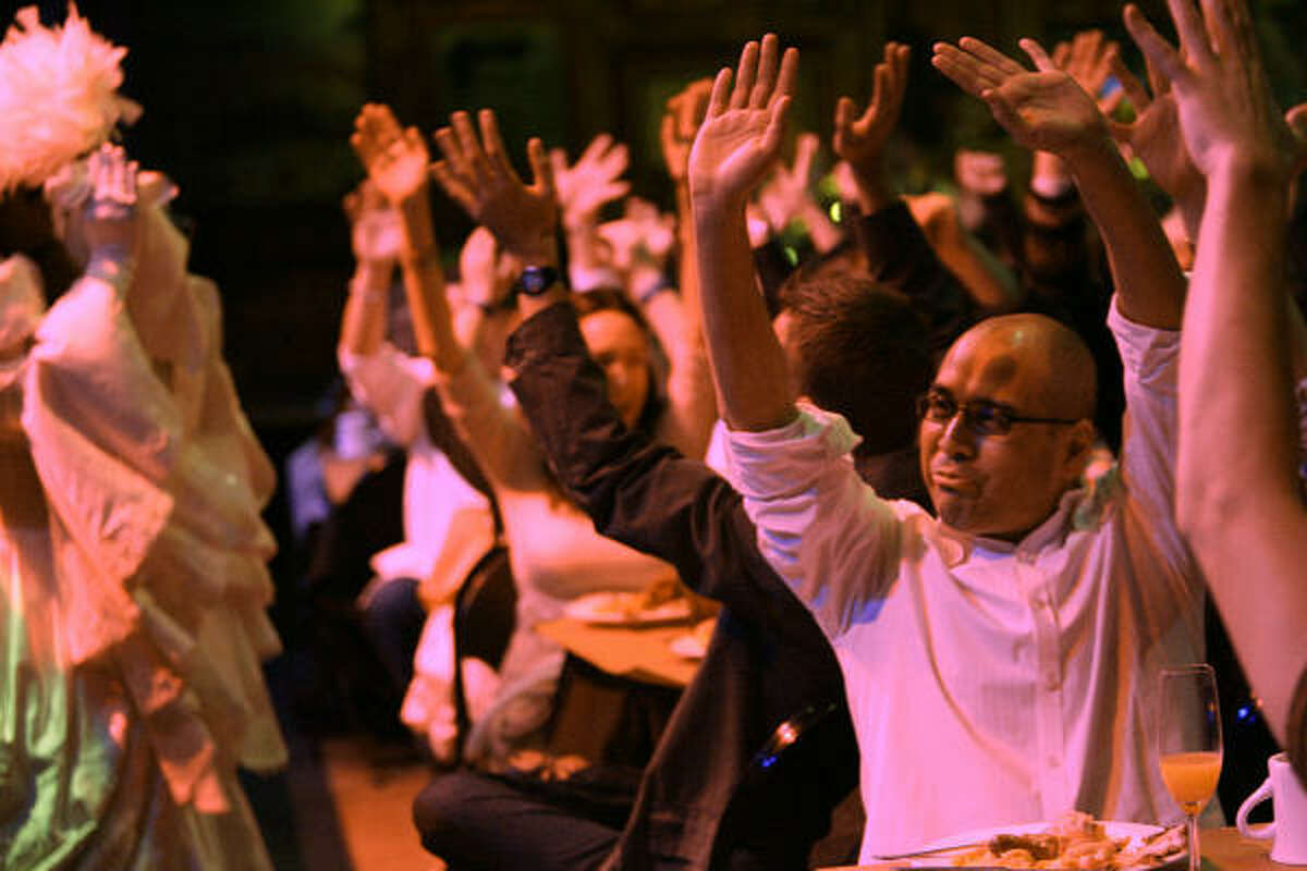 David Gonzales raises his hands as the audience participates with the Hensley Ensemble while they perform during The House of Blues Gospel Brunch on Sunday Jan. 11.