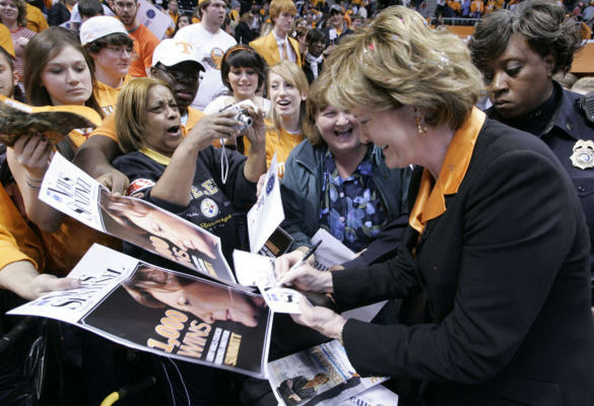 Tennessee coach Pat Summitt, foreground right, signs autographs for fans after winning her 1000th career NCAA college basketball game against Georgia 73-43.