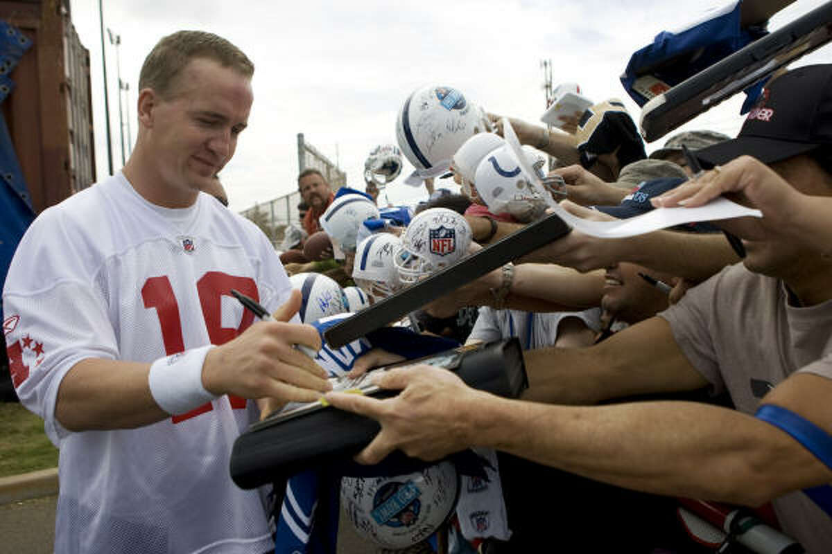 Indianapolis Colts quarterback Peyton Manning signs autographs for fans.