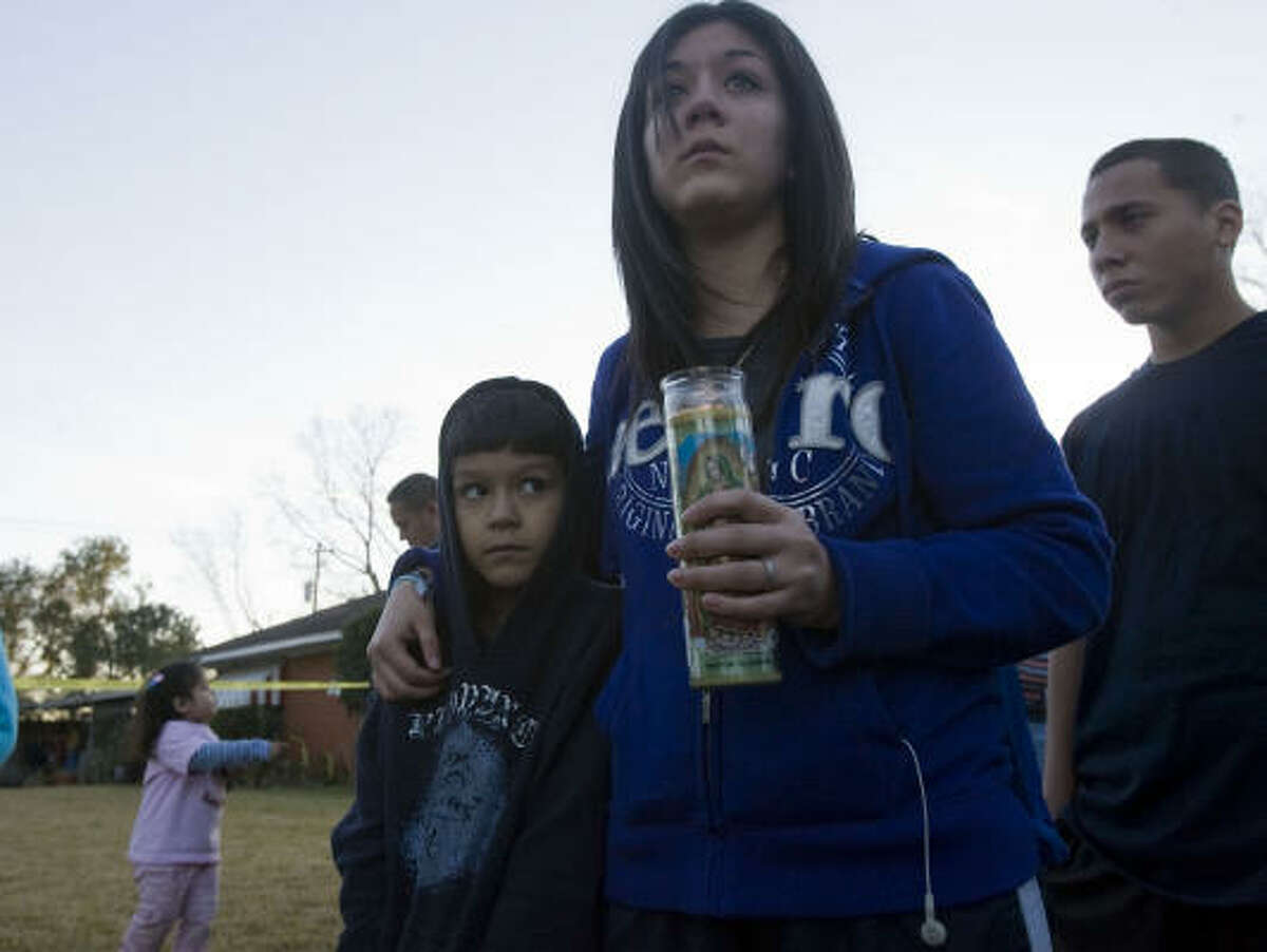 Karen Garza, 16, burns a candle while comforting her brother Isaih Garza, 7, at the scene where a child died in the 500 block of Gilpin Wednesday in Houston.
