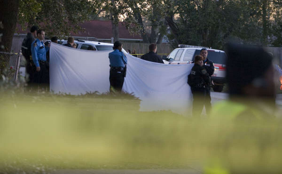 Houston police officers investigate at the scene where a child died in an auto accident in the 500 block of Gilpin Wednesday in Houston.