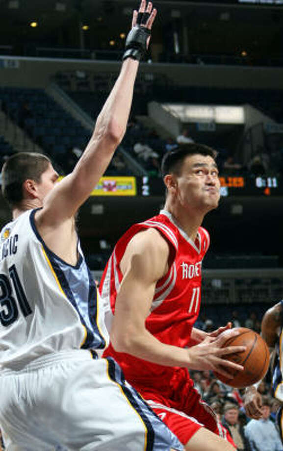 Yao Ming, center, shoots while being defended by Grizzlies forward Darko Milicic in the fourth quarter. Photo: Nikki Boertman, AP