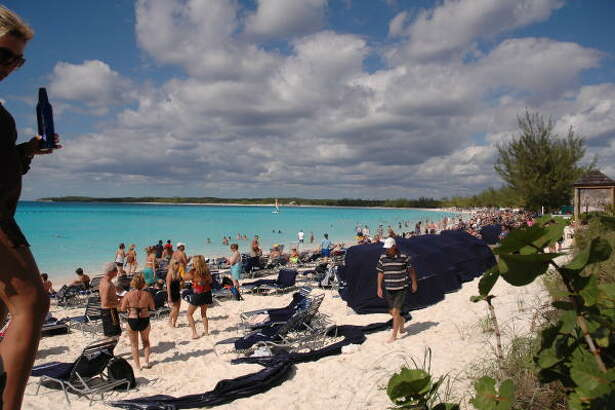 Passengers lounge on the beach, swim or enjoy watersports adventures at Half Moon Cay, Carnival Cruise Lines' private island in the Bahamas. The Carnival Splendor cruise ship is anchored in the background.