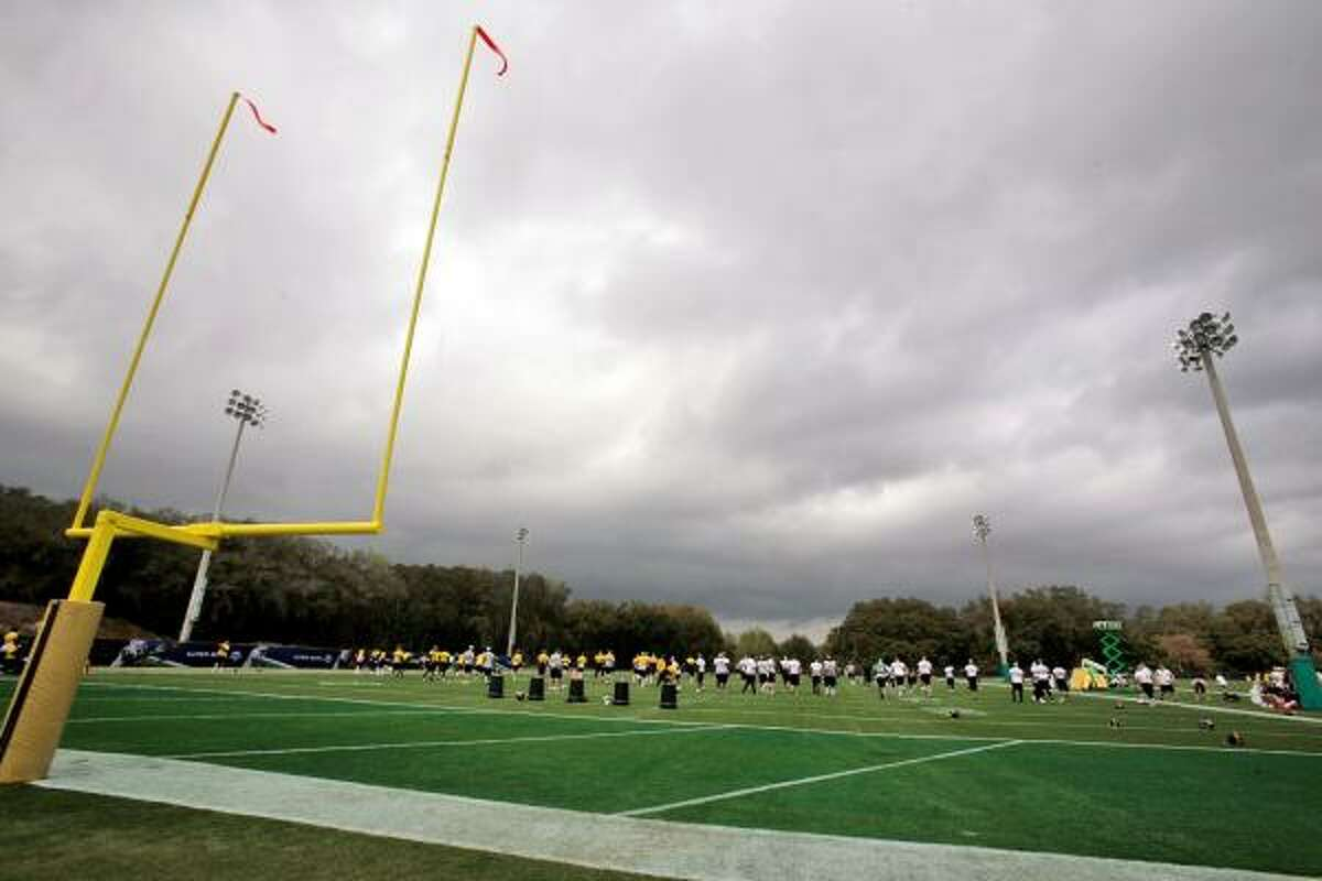 The Pittsburgh Steelers warm up under threatening rain clouds during football practice at the University of South Florida.