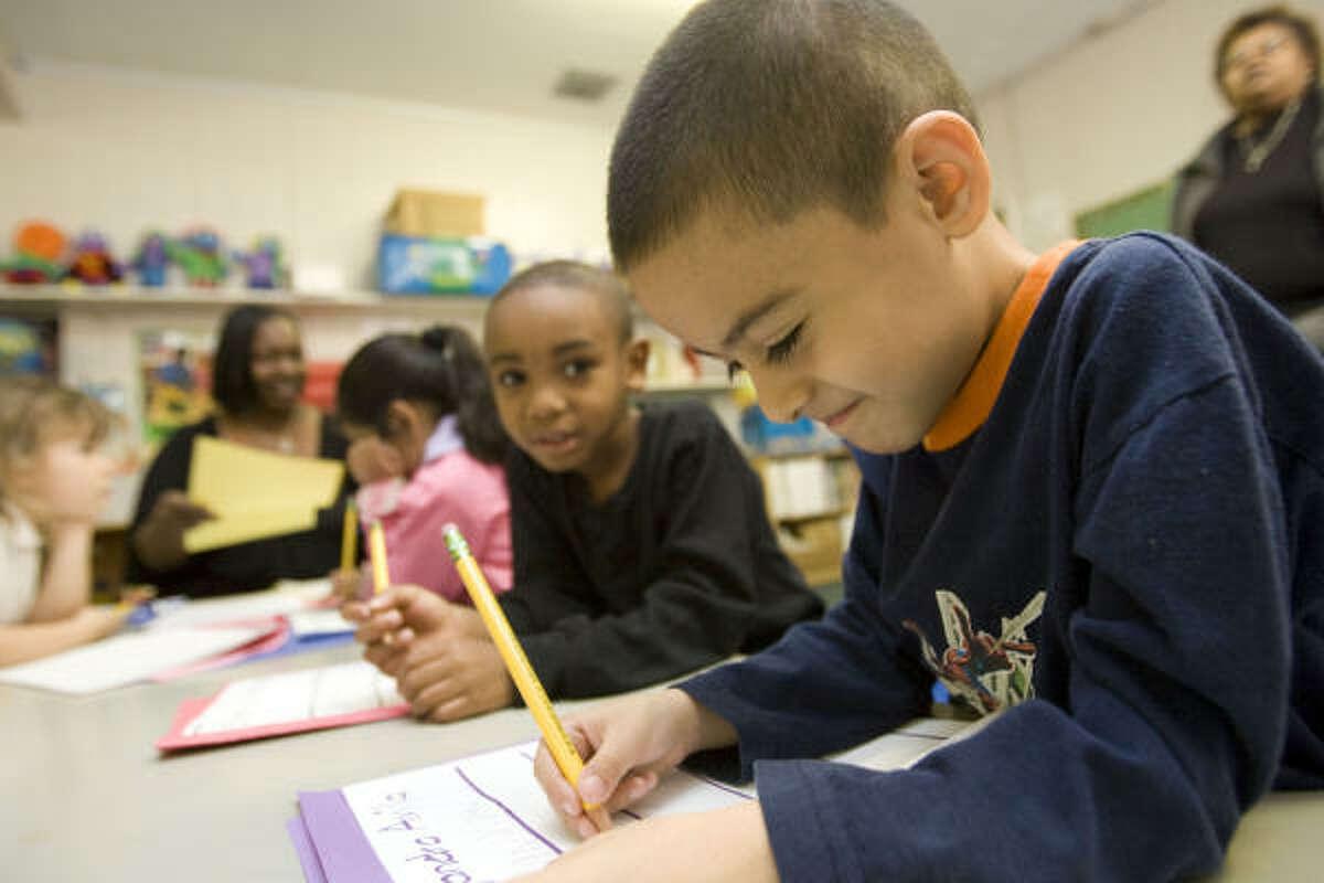 Ta'Von Griffin (centro) y Alejandro Ávila (der.), de cinco años, escriben durante la clase de Head Start en la escuela Sheffield, de Houston, que requiere reparaciones y podría recibir dinero del paquete de estímulo económico.
