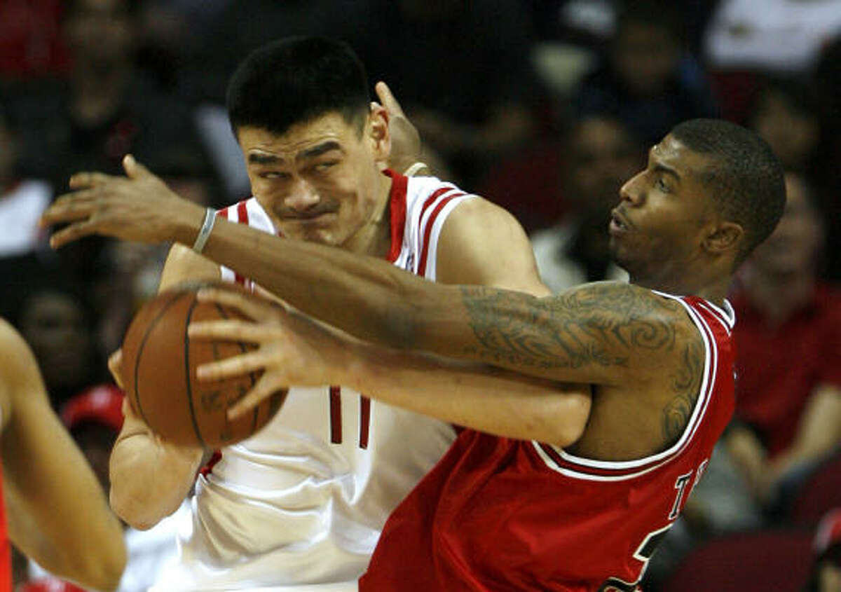 Yao Ming, left, works inside against Chicago's Tyrus Thomas in the second half. Yao matched a game-high with 28 points.