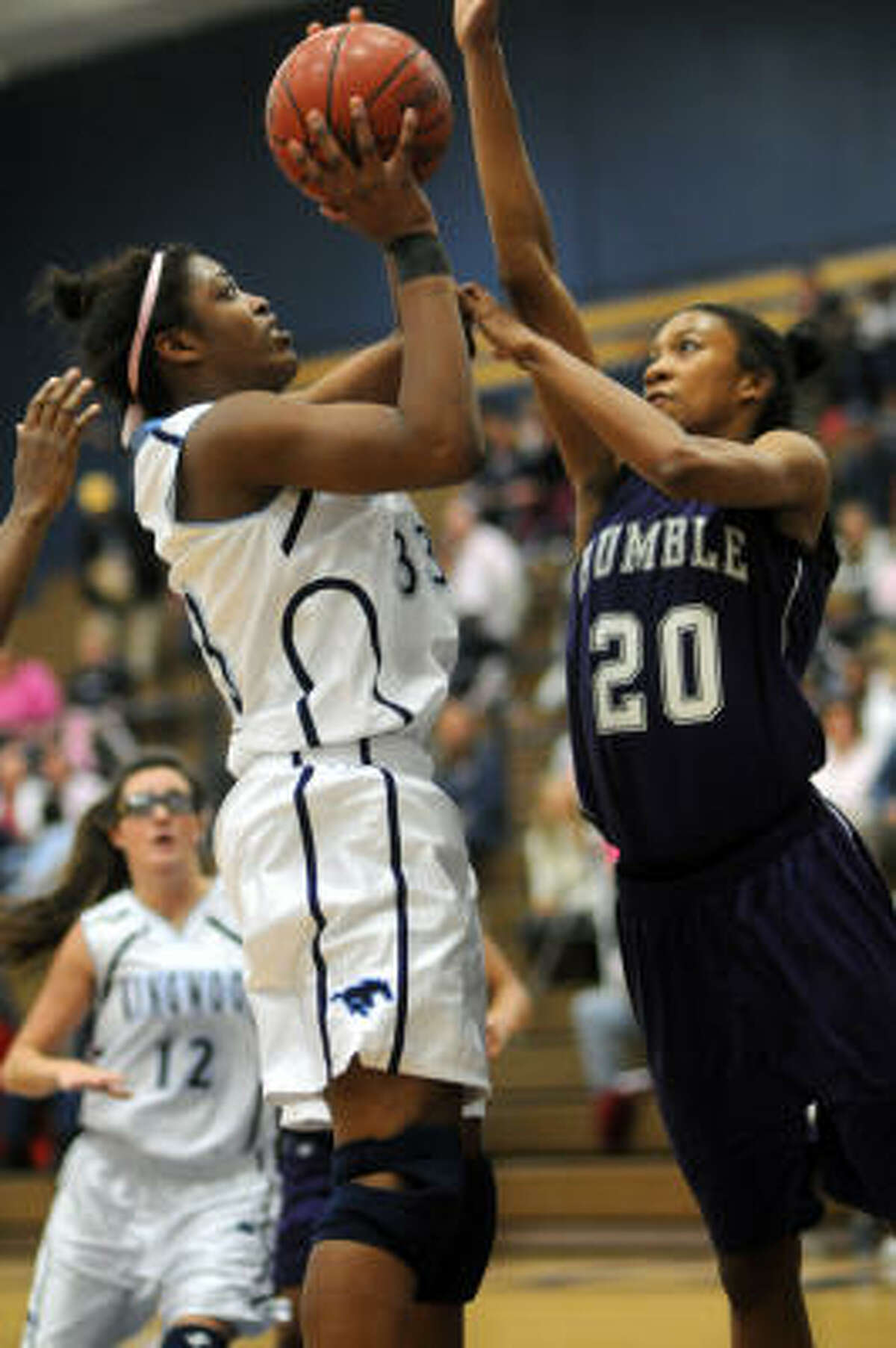 Humble junior Brenea White, right, goes up for a block against Kingwood's senior Michelle Price.