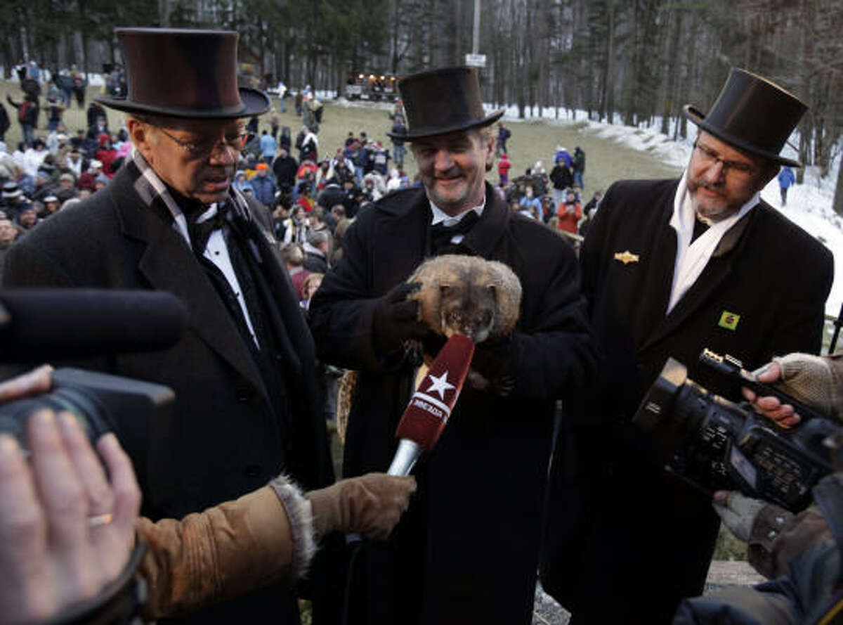 John Griffiths, center, holds weather-predicting groundhog Punxsutawney Phil as Phil is interviewed by media at Gobbler's Knob on in Punxsutawney, Pa.