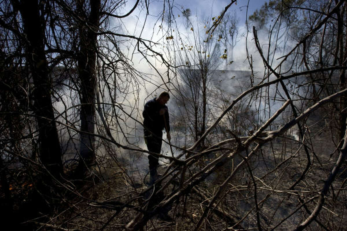Houston firefighter William White works on putting out a grass fire in a wooded area near T.C. Jester Park on Monday in Houston.