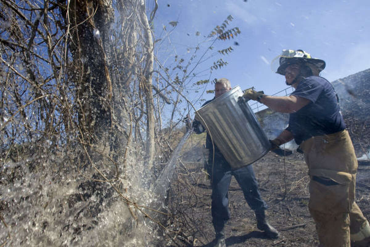Houston firefighters William White, left, and Trey Bourgeois work in a wooded area near T.C. Jester Park on Monday.