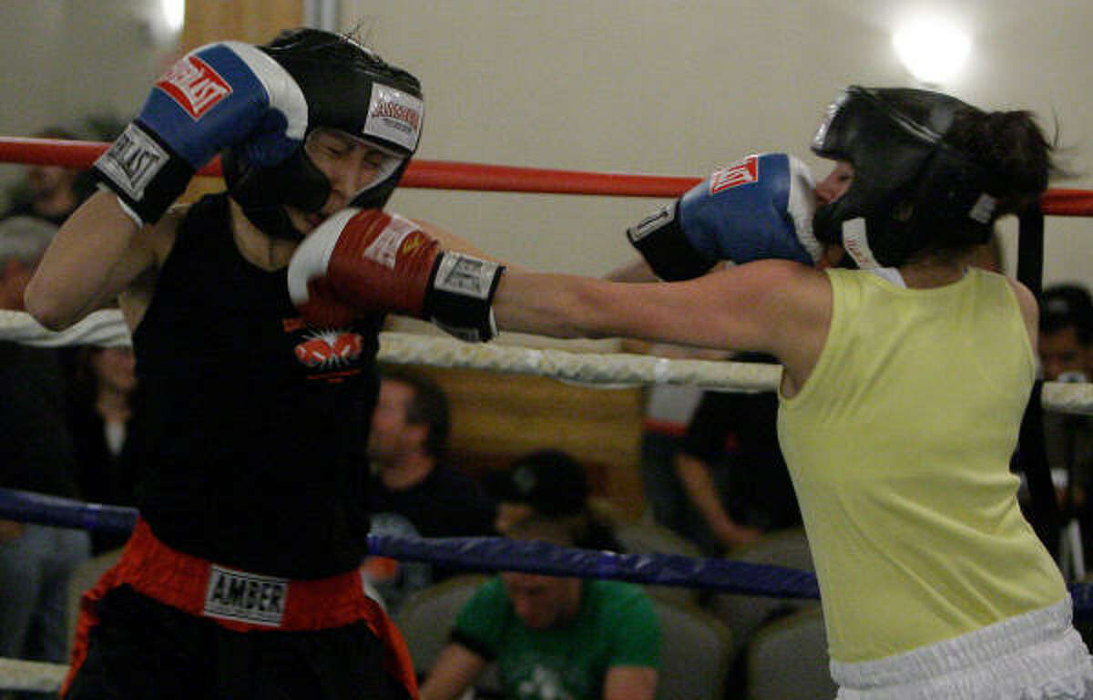 Xochitz Lara exchanges punches with Demi Ayala, right, during the Golden Gloves boxing competition (female all comers 17-34 years 106 weight).