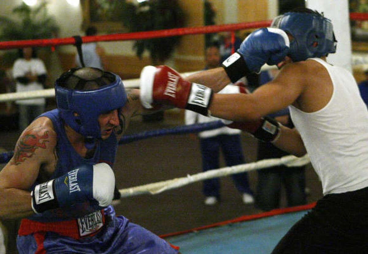 Kelly Barnett, in blue, of Savannah Boxing Gym, fights Elmer Gomez, white, of Main Gym. Barnett won by decision.