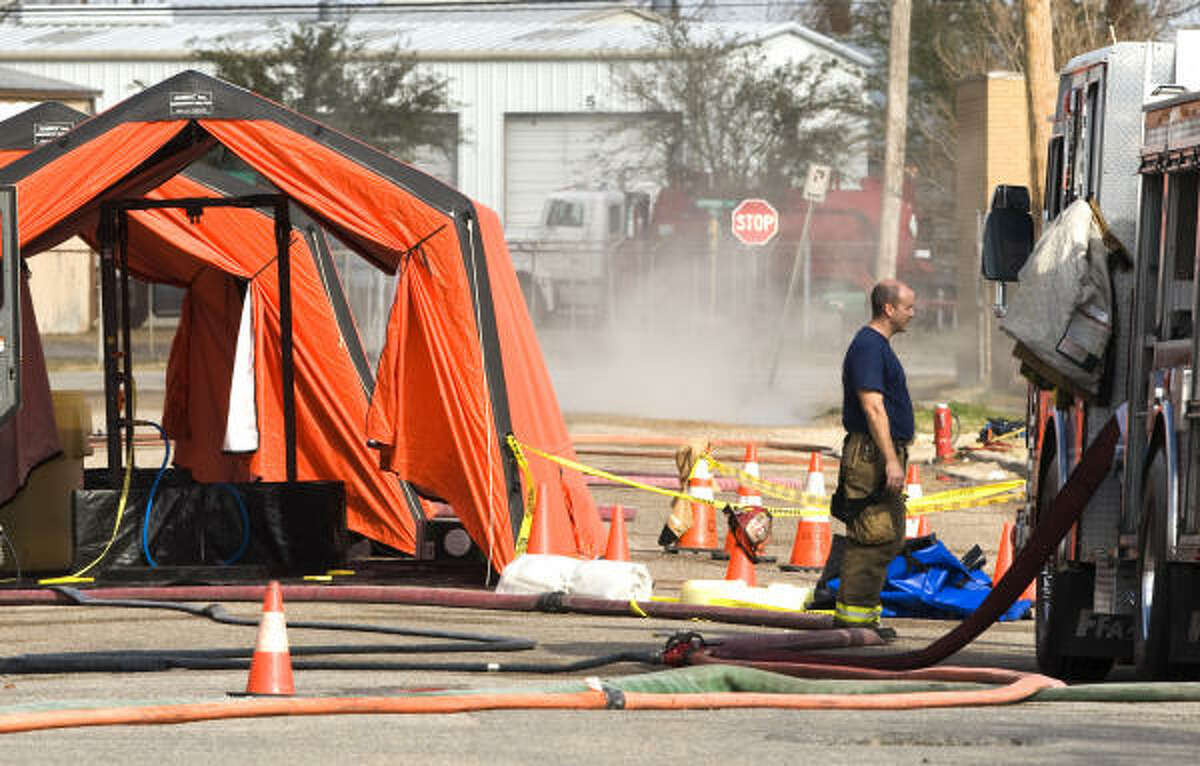 Houston firefighters stand by a decontamination tent as hydrochloric acid vapor is seen in the background Sunday in the 5900 block of Plainview in Houston. There were no injuries reported from the leak.