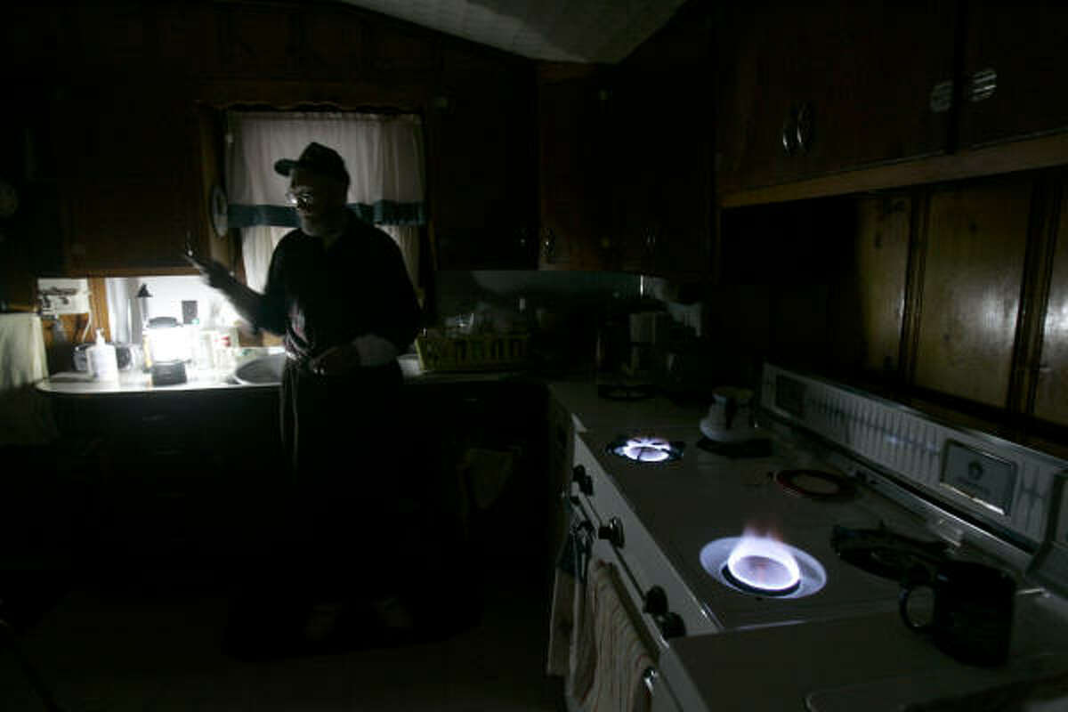 Bob Goins uses a camping stove to see and his kitchen stove for heat in his darkened house Saturday in Mayfield, Ky.