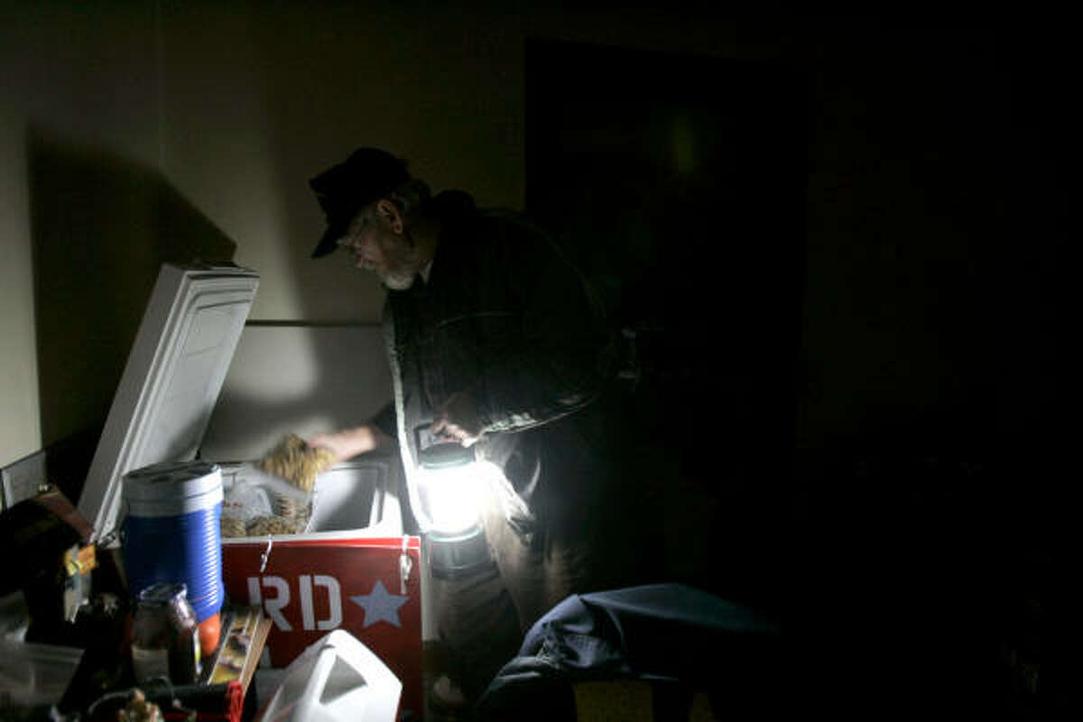 Bob Goins uses a camping light to check on food in a freezer in his dark home Saturday in Mayfield, Ky.