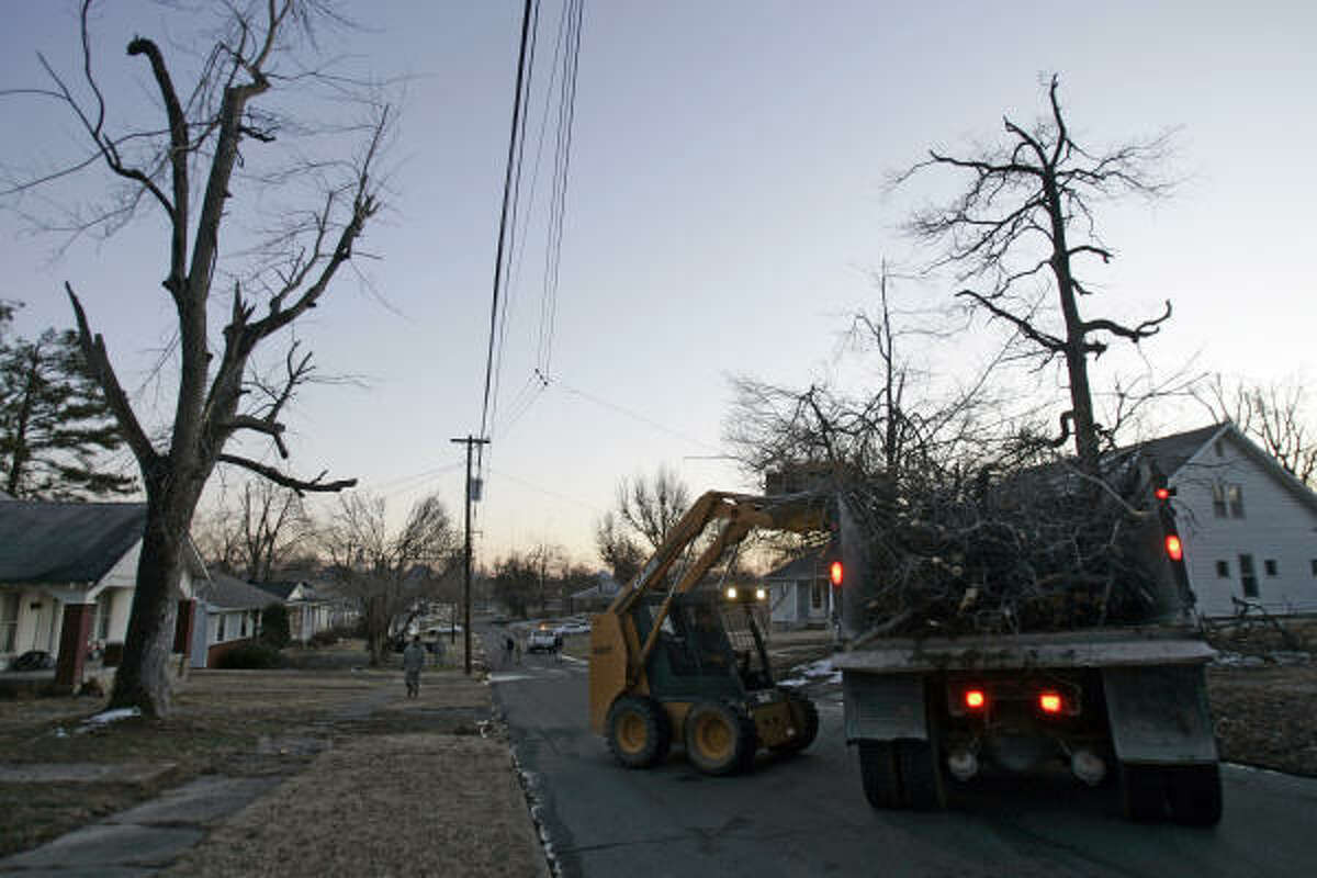 Crews work to clear storm debris from the streets Saturday in Mayfield, Ky.