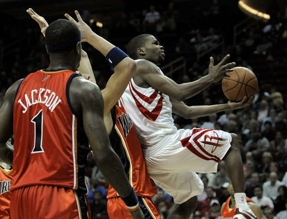 Aaron Brooks, right, drives to the basket in front of Golden State defenders Stephen Jackson (1) and Andris Biedrins, center, during the second half. Brooks matched his career-high with 22 points and and played the entire fourth quarter.