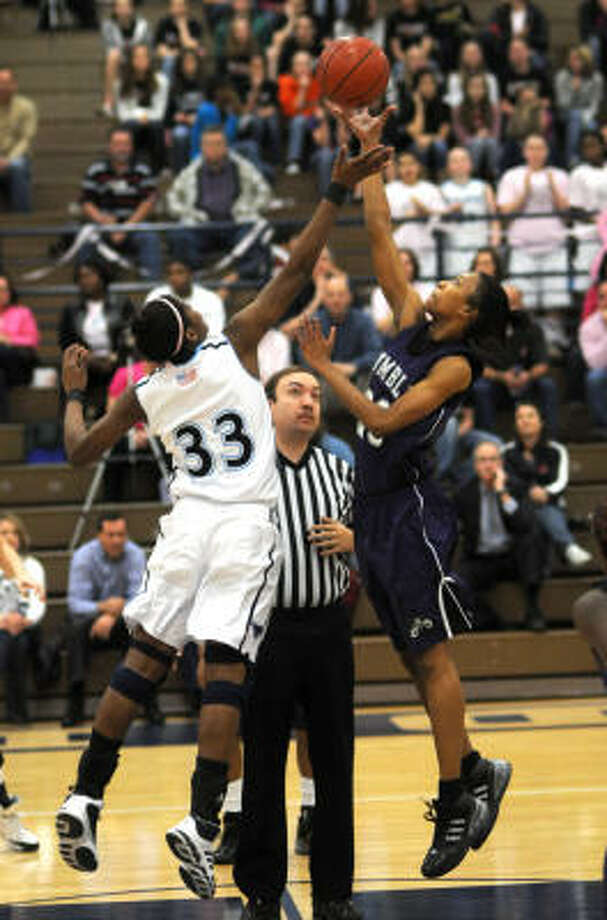 Humble junior Brenea White, right, wins the opening tip against Kingwood's senior Michelle Price. Photo: Jerry Baker, For The Chronicle