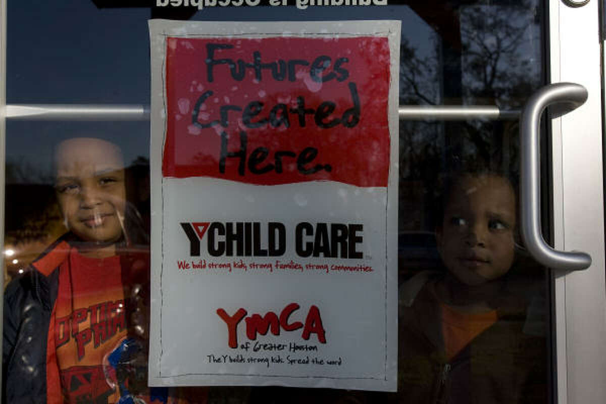 Dante Jefferson Jr., 4, (left) and Jaden Jefferson, 3, wait for their father at a YMCA day-care center in Houston. About 800 fewer children a day are coming to YMCA centers in the city.