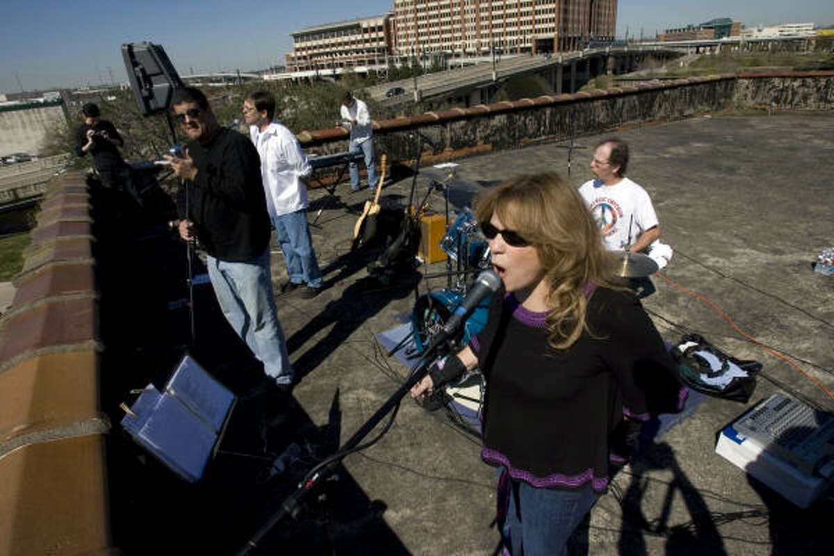 Myrna Sanders, a singer with the Love Street Light Circus band, performs Beatles songs on top of the International Coffee Building downtown as part o the tribute to the Beatles' final performance 40 years ago.