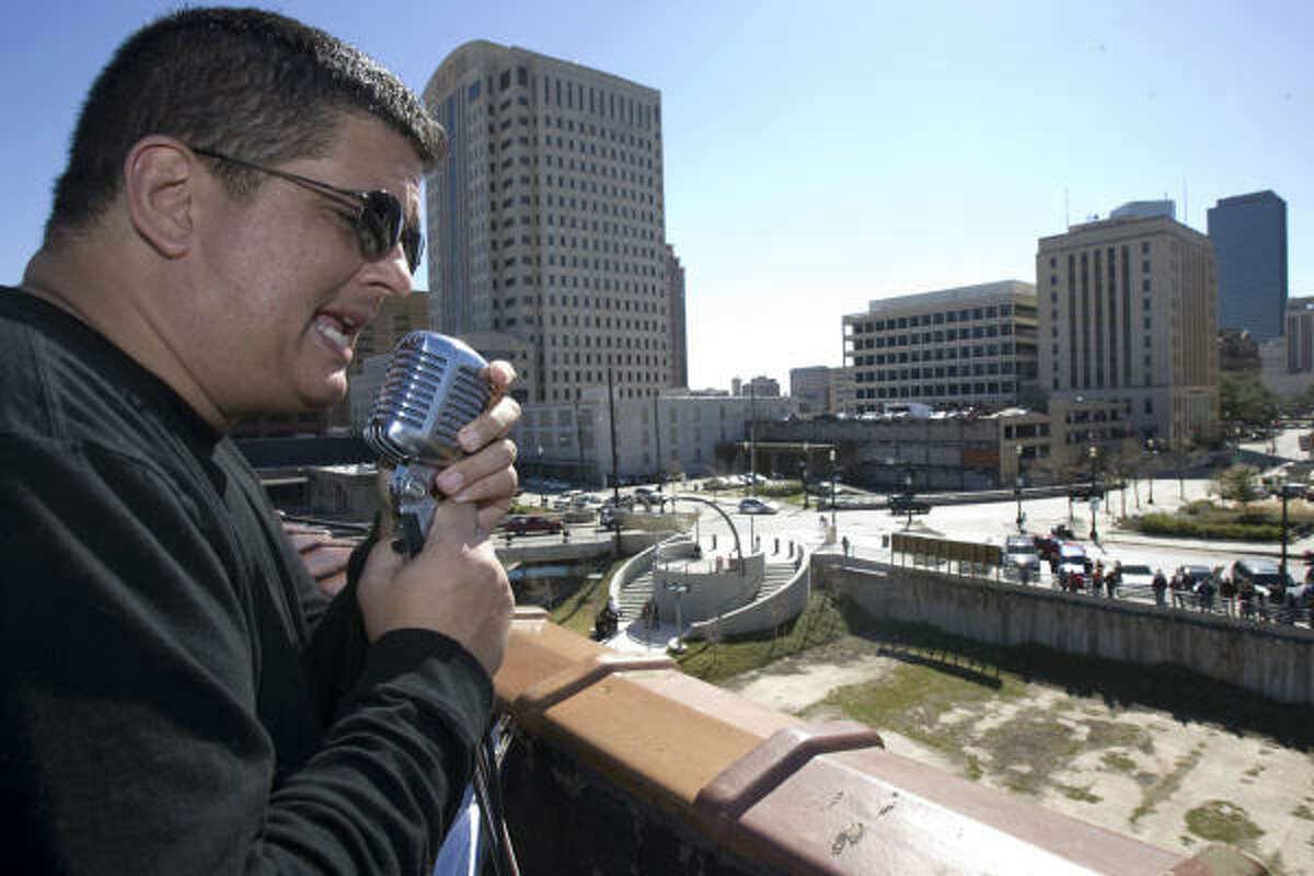 Jon Bouche, a singer with the Love Street Light Circus Band, performs Beatles songs on top of the International Coffee Building downtown Friday. The group performs to raise money for children's charities.
