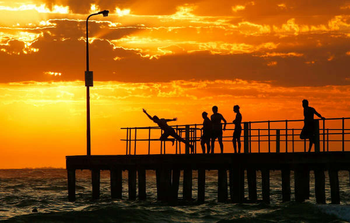 People dive into the sea from the pier at St Kilda beach in Melbourne, Australia.