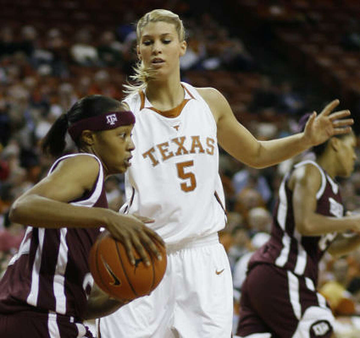 Texas A&M forward Tanisha Smith, left, tries to get by Texas guard Kathleen Nash after pulling in a rebound in the first half.