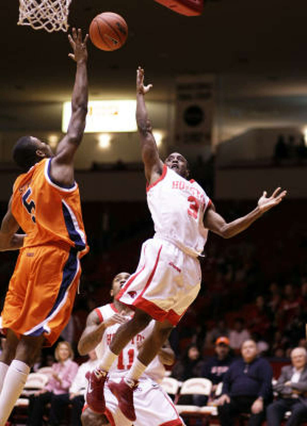 UH guard Desmond Wade (right) drives to the basket past UTEP's Julyan Stone during the first half.