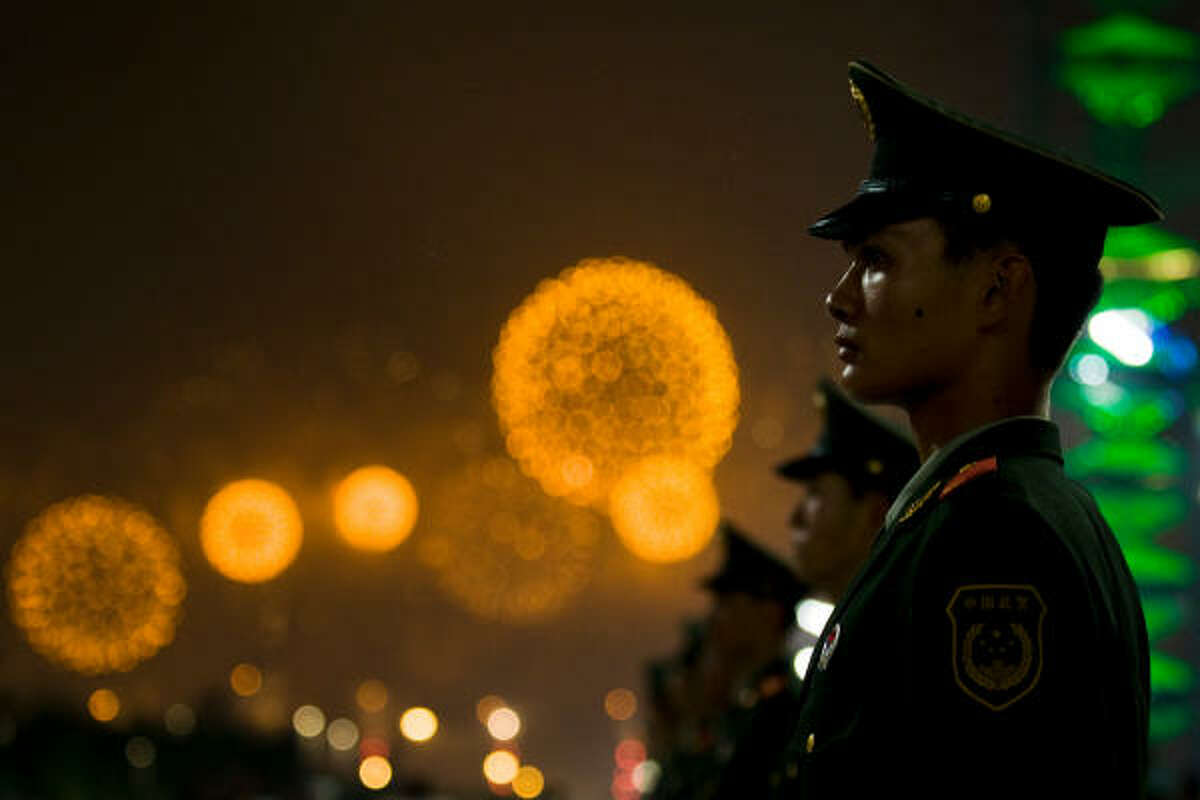 Guards line the Olympic Green as fire works explode as part of the closing ceremonies for the 2008 Summer Olympic Games in Beijing.