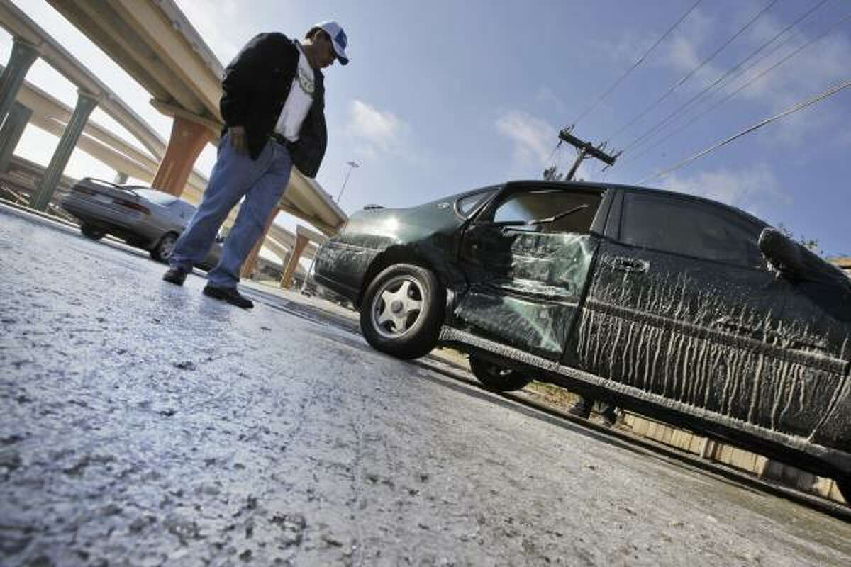 Miguel Angel Cruz looks at a car damaged after sliding on a patch of ice in Dallas Wednesday. An overnight ice storm left North Texas coated in ice.