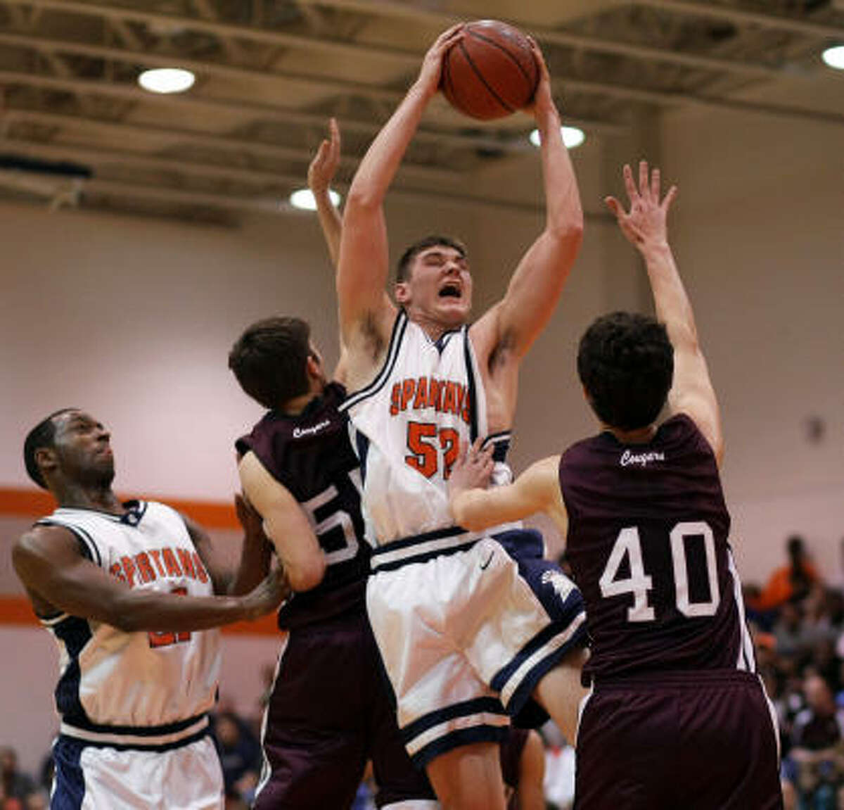 Seven Lake's Brendan Flower grabs a rebound over Cinco Ranch's Thomas Donnellty (40).