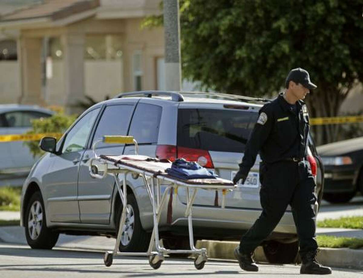 A Los Angeles coroner official carries a stretcher into the Lupoe home.