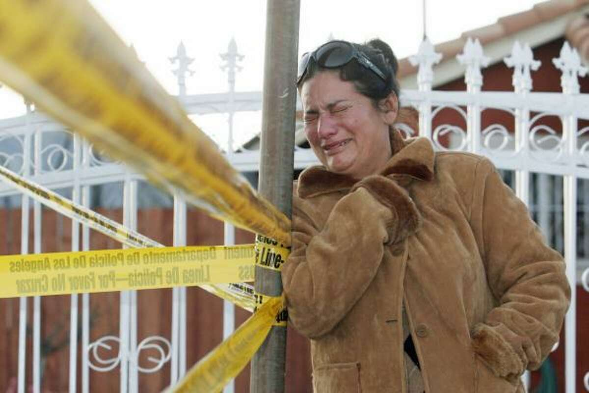 Audelia Birucel, who was visiting relatives in the neighborhood, cries after learning that a man apparently distraught about losing his job killed his wife and five children before committing suicide in a two-story tract home in Wilmington, Calif.