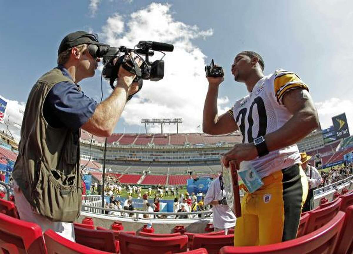 Pittsburgh Steelers Roy Lewis films a cameraman while being interviewed during the team's media day for Super Bowl XLIII Tuesday.
