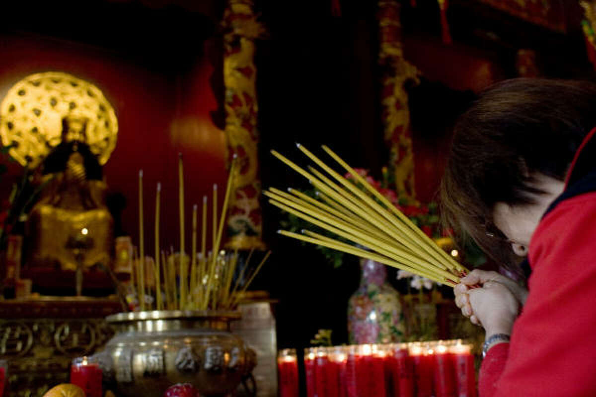 Anni Wong prays at an altar at the Teo Chew Temple in celebration of the Chinese Lunar New Year Monday.