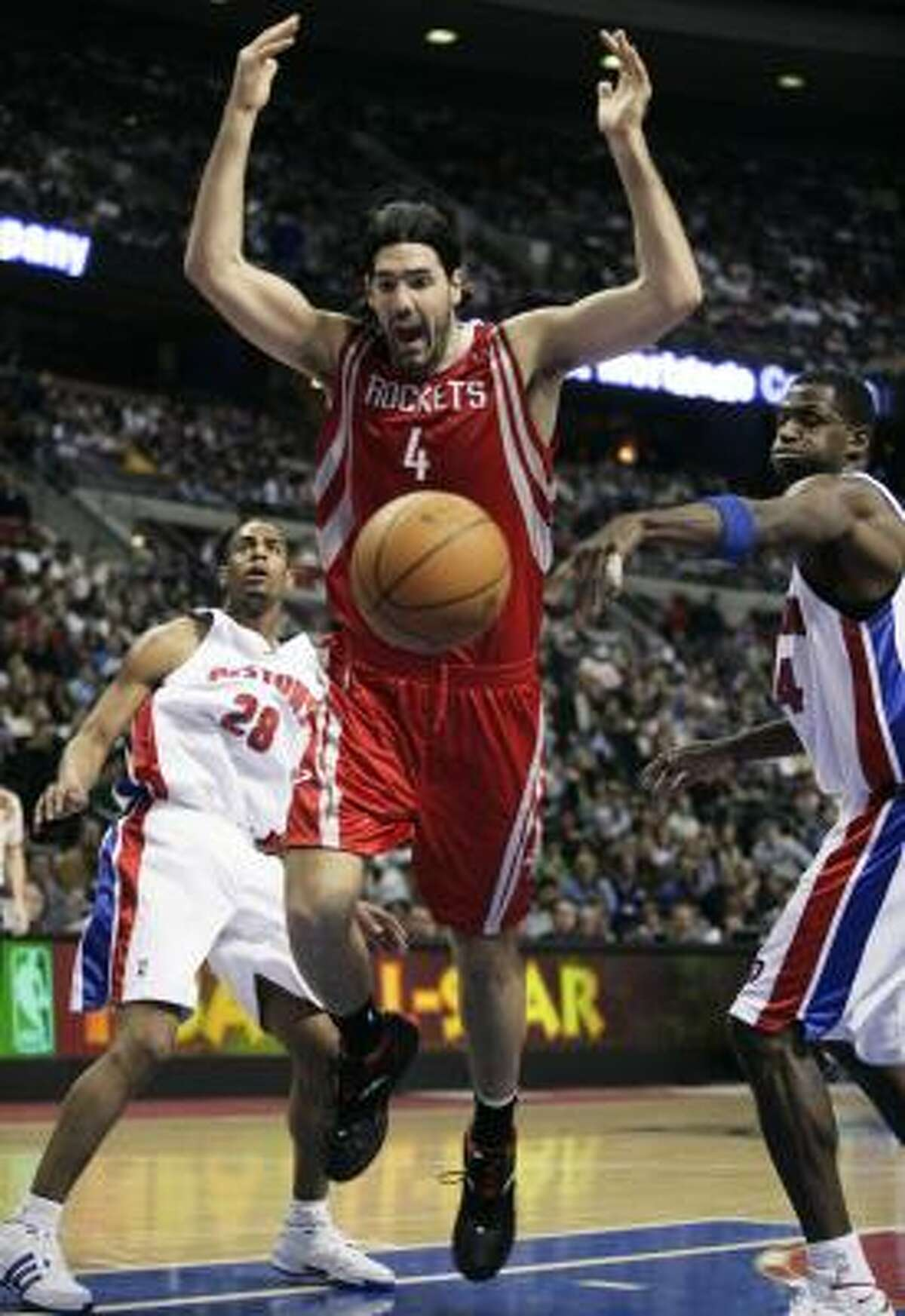 Luis Scola spins out of control while driving to the basket against Piston defenders Arron Afflalo, left, and Antonio McDyess in the first half.