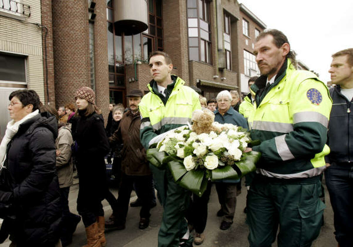 Mourners carry flowers during a march to the Fabeltjesland daycare center.