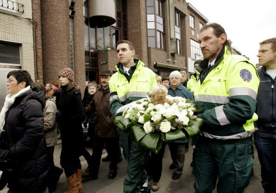 Mourners carry flowers during a march to the Fabeltjesland daycare center. Photo: Virginia Mayo, AP