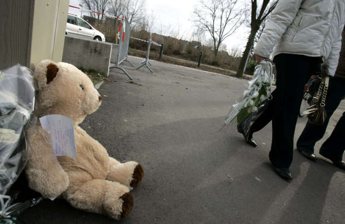 A woman walks with flowers past a teddy bear placed at a memorial at the Fabeltjesland daycare center.