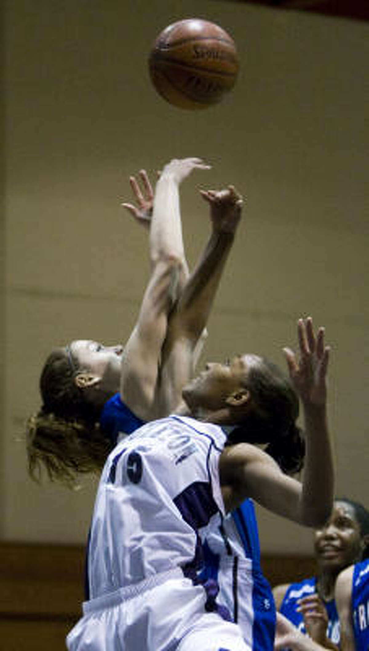 Friendswood's Cheraz Spozio, left, and Angleton's Ceteria Foster (15) go up for a rebound during the first half.