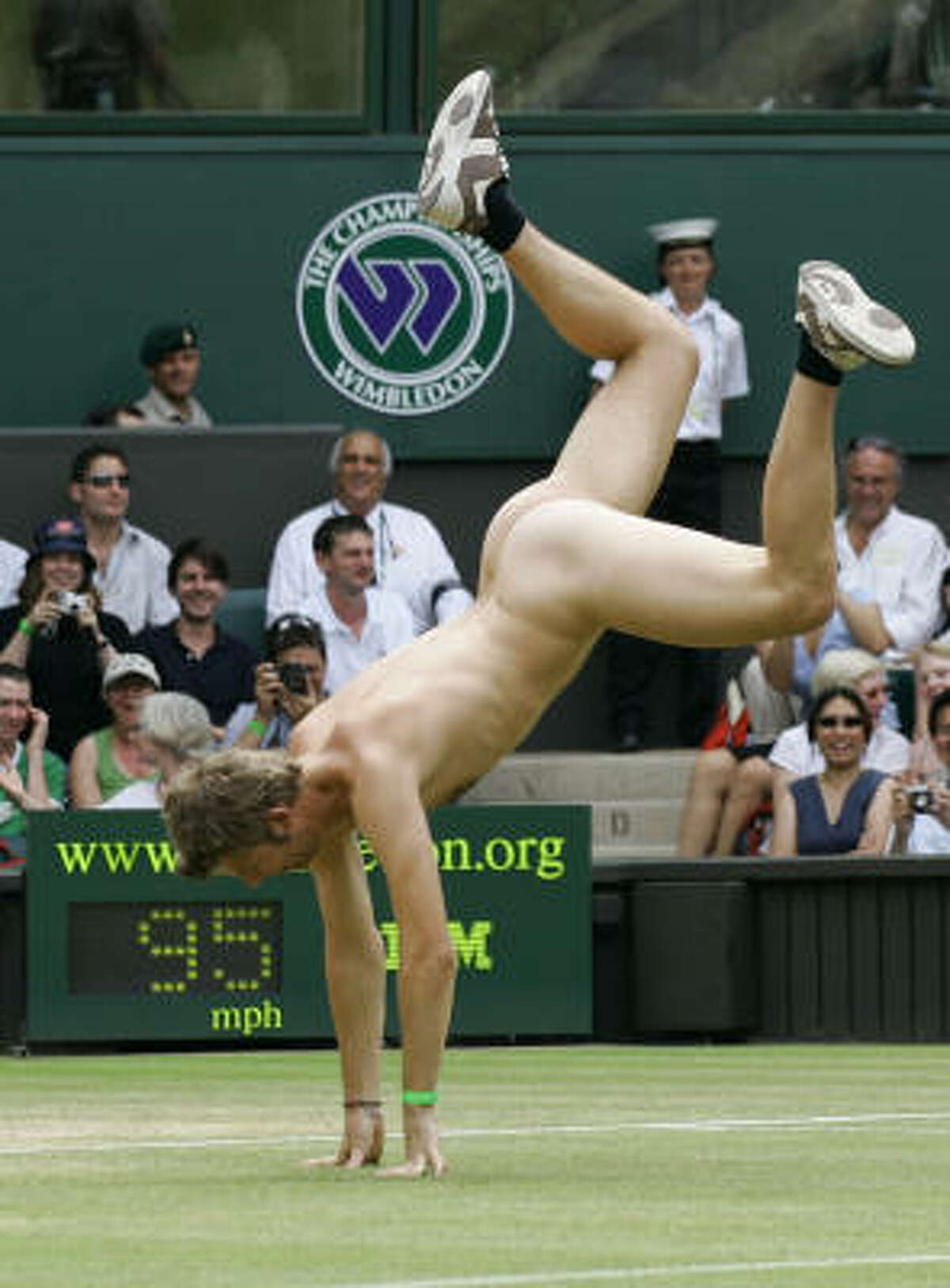 ** FOR USE WITH YEAR END--FILE **An unidentified streaker does a cartwheel, as he interrupts the Women's Singles quarter-final match between Maria Sharapova and Elena Dementieva, both of Russia, on the Centre Court at Wimbledon, in this July 4, 2006, file photo.