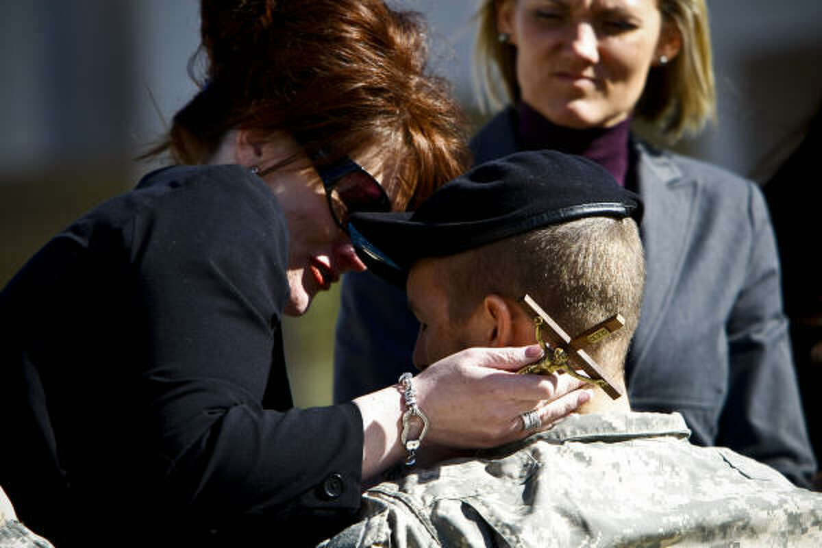 Kristi Mitts, widow of Charles Mitts, talks with Lt. Ellis Taylor, the pilot of the Blackhawk helicopter that crashed January 12 in College Station, before the start of the burial service for Charles Mitts.