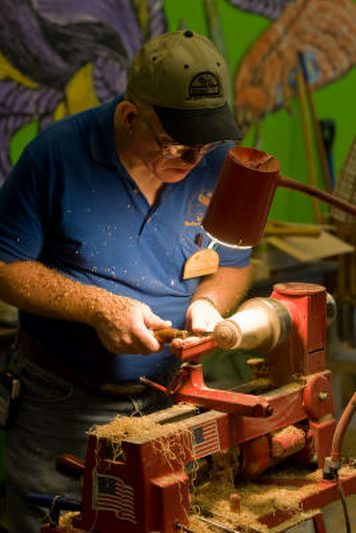 Jonathan Bartz turns a top on a lathe.
