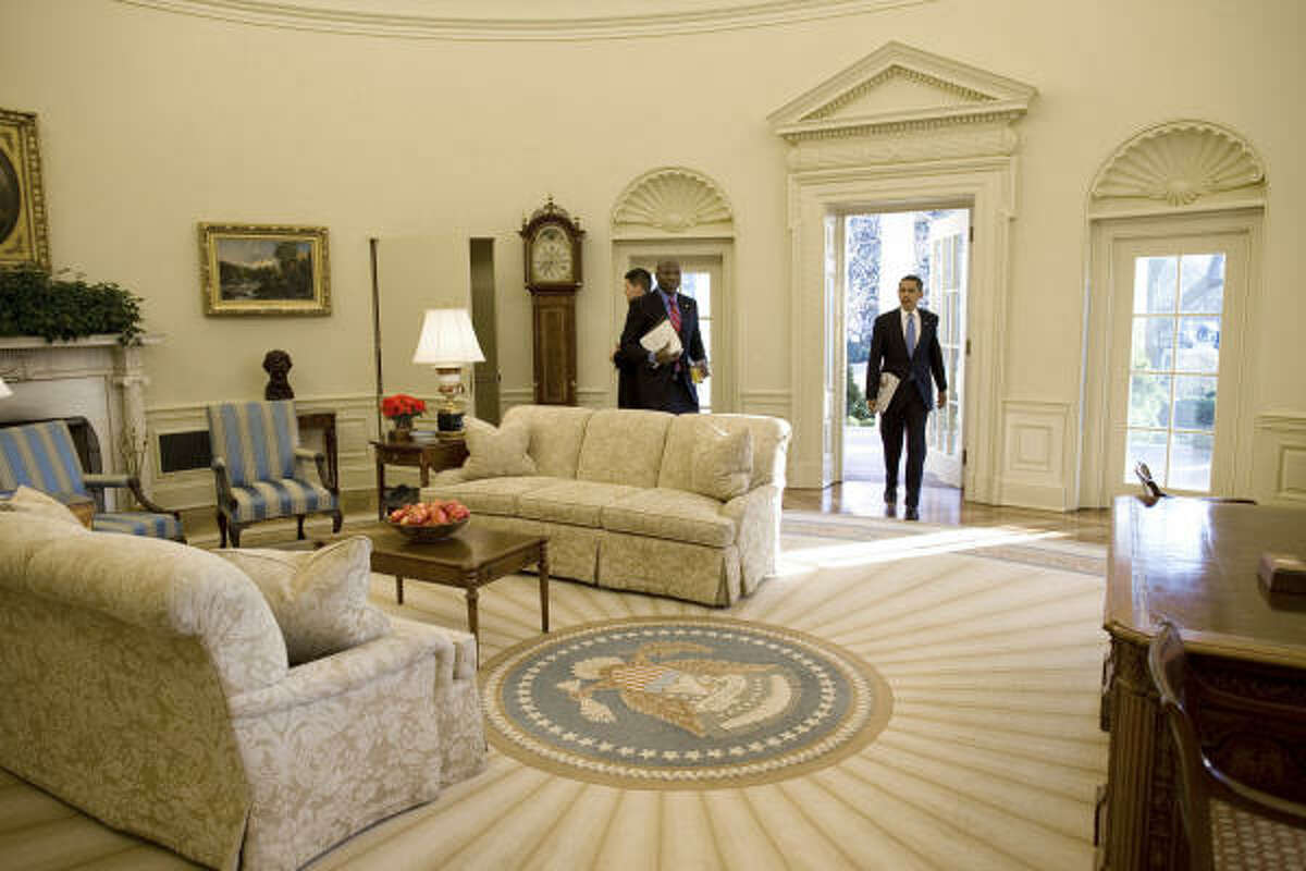 President Barack Obama walks into the Oval Office of the White House Wednesday morning to begin the first full day of his administration.
