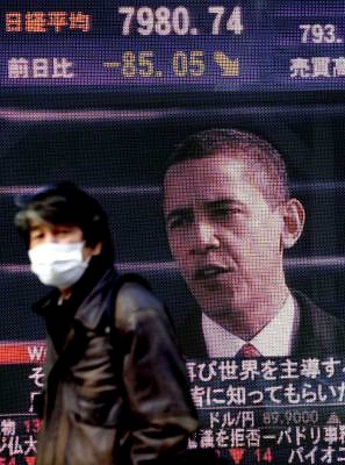 A man walks past an electronic stock board in Tokyo, Japan, indicating the Japanese stock dropped Jan. 21 while showing U.S. President Barack Obama at the inauguration ceremony in Washington.