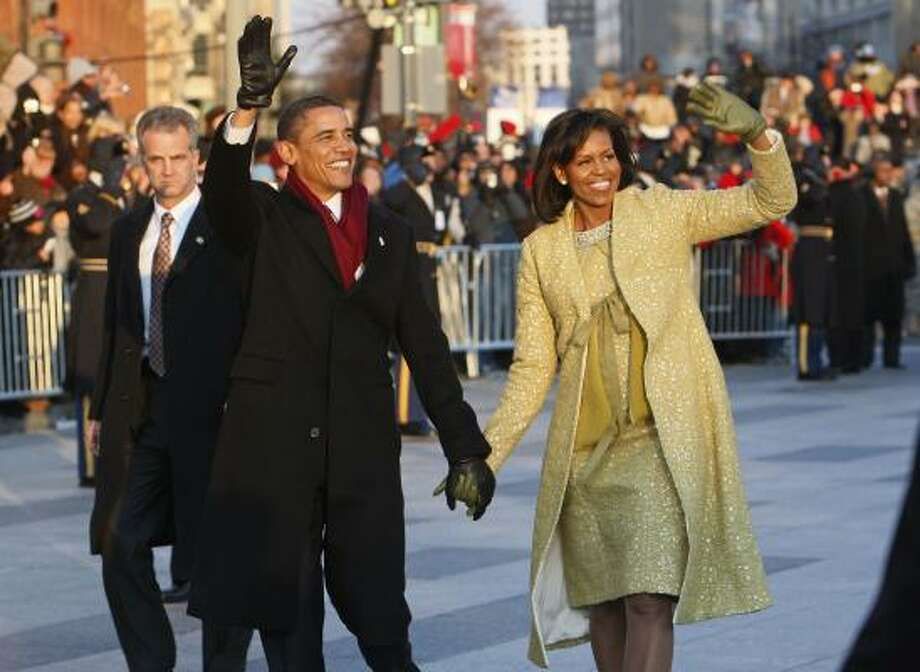 President Barack Obama and first lady Michelle Obama walk the inaugural parade route in Washington Tuesday. Photo: Charles Dharapak, AP