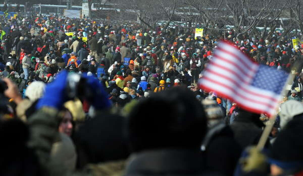 People rush to watch the inaugural parade after Barack Obama was sworn in as president in Washington Tuesday. Some two million people erupted in joyous celebration, cheering and waving flags as Obama took the oath of office.